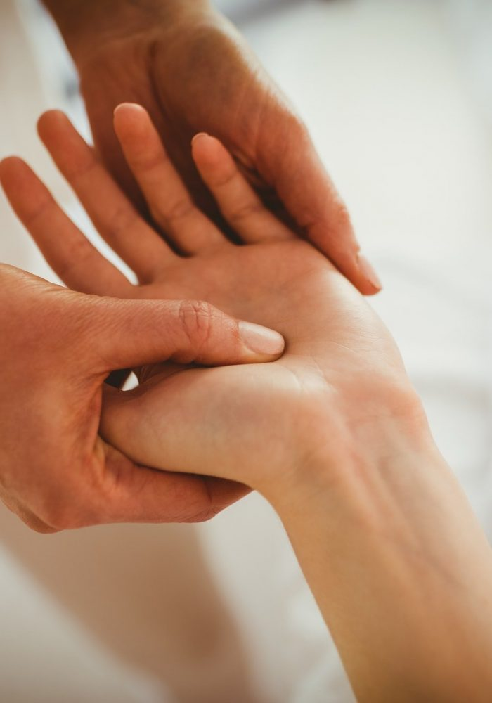 Young woman getting hand massage in therapy room